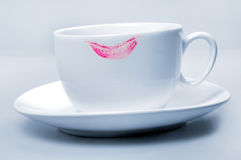 Lipstick pink on white cup. On blue background stock photo