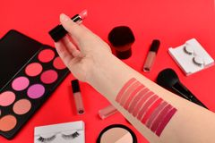 Lipstick swatches on woman hand. Professional makeup products with cosmetic beauty products, foundation, lipstick,  eye shadows,. Eye lashes, brushes and tools stock photo