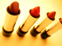 Lipstick Tubes. 4 tubes of reddish toned lipstick on orange background. Light shadows. Focus on front tubes stock photo