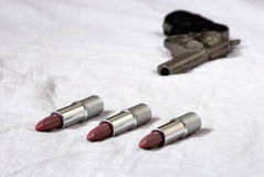 Lipsticks in the bed. Red lipsticks in the bed with pistol Royalty Free Stock Image