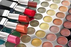 Lipsticks on eye shadow palette Royalty Free Stock Photos