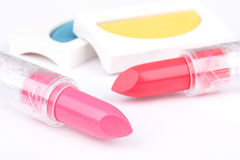 Lipsticks and eyeshadows on white Stock Photos