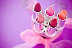 Lipsticks and lipglosses with bow Royalty Free Stock Photos