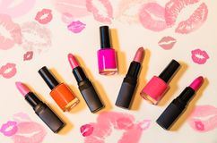 Lipsticks and nail polishes on beige background. Set of lipsticks and nail polishes on beige background Stock Photography