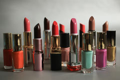 Lipsticks and nail polishes - cosmetics set on a gray background Stock Photography