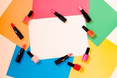 Lipstics and nail polishes on colorful paper background. Different lipstics and nail polishes on colorful paper background Royalty Free Stock Image