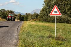 Liptovsky Hradok, Slovakia - August 22nd, 2018: Caution cows crossing sign, next to road with tractor coming, countryside, hills royalty free stock photography