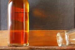 Liqour-Flasche und schmutziges Schnapsglas stellen den Alkohol und das alco dar lizenzfreie stockbilder
