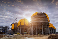 Liquefied Natural Gas LNG storage tanks in construction. Refinery storage tanks . A large oil-refinery plant with Liquefied Natural Gas LNG storage tanks in Royalty Free Stock Images