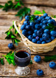 Liqueur from blueberry in a shot glass. Style rustic. selective focus Royalty Free Stock Images