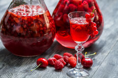 Liqueur made of wild berries and alcohol. On old table royalty free stock image