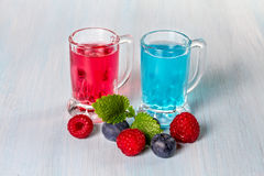 Liqueur of raspberry and blueberries. With fresh berries Stock Photos