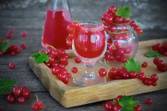 Liqueur of red currant in the glass. And fresh berries on the old background royalty free stock photo