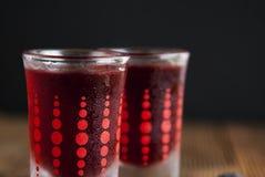 Liqueur rouge de baies dans le verre à liqueur d'isolement sur le fond noir et la table en bois Concept fait maison de boissons d photographie stock
