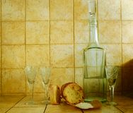 Liquid in a bottle, wineglasses, bread and salt Royalty Free Stock Image