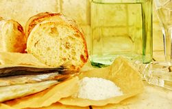 Liquid in a bottle, wineglasses, bread and salt Stock Photos