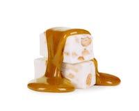 Liquid caramel runs down the candy nougat Stock Photos