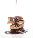 Liquid chocolate, falling into group of pieces of chocolate on w Royalty Free Stock Images