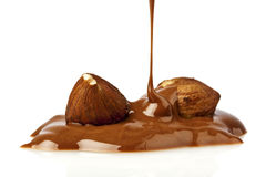 Liquid chocolate and hazelnuts. Liquid chocolate flowing over hazelnuts Stock Image