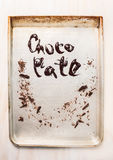 Liquid chocolate inscription on metallic baking tray Royalty Free Stock Photos