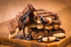 Liquid chocolate thread falls on chocolate pieces Royalty Free Stock Image
