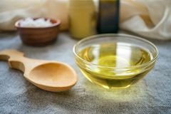 Liquid coconut MCT oil in round glass bowl with wooden spoon and stock images