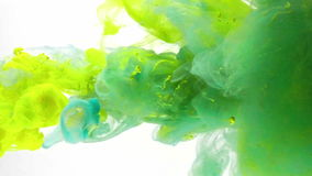 Liquid colors mixing under water. Liquid Colors droped mix in moving in dynamic flow. Ink slowly swirling injected in water. Ink poured and isolated on white stock footage