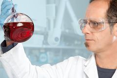 Liquid consistent check. A Chemist is checking the consistency of a red Liquid royalty free stock image