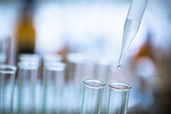 Liquid drop from laboratory glass pipette Royalty Free Stock Photos