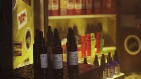Liquid for electronic cigarettes at stand in nightclub. Spotlights. Steam. stock footage