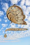 Surreal Alarm clock transforming and thawing on blue sky backgro Stock Photo