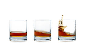 Liquid in a glass. A lapping alcohol in three glasses on a white background Royalty Free Stock Photography
