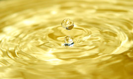 Liquid gold and a drop. Gold-like liquid Stock Images