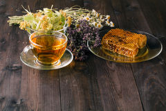 Liquid honey with honeycomb and tea cup inside bunch of dry herb Royalty Free Stock Image