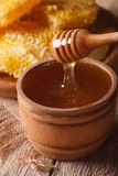 Liquid honey in a wooden bowl with a stick close-up. vertical Royalty Free Stock Images