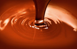 Liquid hot chocolate pouring. Chocolate flow. Close up of liquid hot chocolate pouring closeup Royalty Free Stock Photo