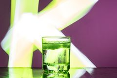 Liquid with ice in a glass on a reflective surface on a reddish background royalty free stock image