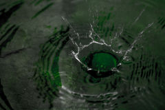 Liquid impact. Water rop impacting on water Stock Photography