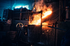 Liquid iron flowing in steelworks. Industrial details of metallurgic factory or plant. Details of smelting metal. Iron flowing in steelworks. Industrial details Stock Images