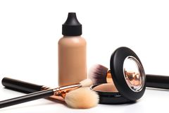 Liquid makeup foundation cream and  shadow, blush, powder, sculptor in a pack with make up brushes on a white background. Isolated. On white. - Image stock photo