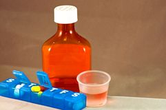 Liquid medication and pills Stock Images