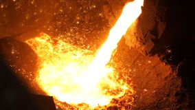 Liquid metal from blast furnace. Liquid iron from ladle in the steelworks.  royalty free stock photography