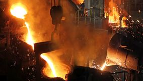 Liquid metal in the foundry. Melting iron in furnace, steel mill. Workers controlling iron smelting in furnaces stock image