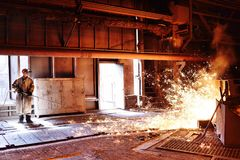 Blast furnace at a metallurgical plant. Liquid metal is poured into molds. Worker, controlling the melting of metal in furnaces. A man works at a metallurgical stock photos