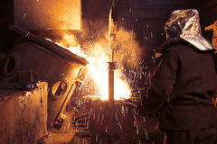 The liquid metal is poured into molds. Worker controlling metal melting in furnaces. Workers operates at the. The liquid metal is poured into molds royalty free stock image