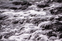 Liquid Motion. The pacific ocean gliding over rocks as it breaks on a hawaiian beach in Keaukaha Stock Images