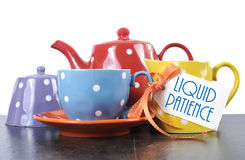 Liquid Patience cup of tea. Red, blue, yellow, orange and purple polka dot tea set with teapot, milk jug creamer, sugar bowl and tea cup with sample text Liquid Royalty Free Stock Image