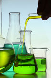 Liquid Pouring into a Flask. Yellow liquid pouring from test tube into a glass flask Royalty Free Stock Photo