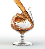 Liquid pouring into a glass. Liquid pouring into a whiskey glass, on white background Stock Photography