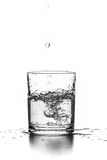 Liquid pouring into a glass. On a white background Royalty Free Stock Image